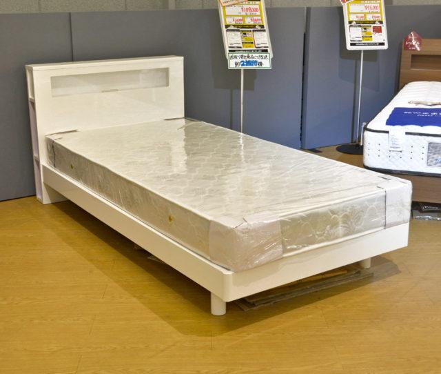 エナメル鏡面塗装仕上げで光沢感のあるホワイトのベッドフレーム!コンセント付きで側面には収納棚もあり便利!通気性の良いすのこ天板で湿気がこもりにくい!