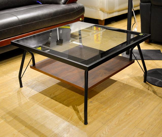 グレーガラスと黒枠フレームの組み合わせがカッコイイ!正方形タイプのリビングテーブル。天板は6mmの強化ガラスを使用しているので強度抜群!天板下に棚板が付いているので雑誌やティッシュなどをサッと収納できる!特徴的な脚部も◎